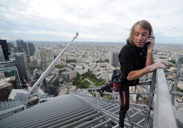 Robert fala ao celular após chegar ao topo. A escalada em Paris foi feita com autorização, o que foge ao seu histórico. O francês costuma subir os prédios sem permissão, fatos pelos quais já foi preso, inclusive no Brasil, em 2008.  Essa é uma nova marca para o 'Homem-Aranha francês', que possui 66% de deficiência no corpo e sofre vertigem desde 1982, quando sofreu uma queda de 15 metros. (Foto: Franck Fife/AFP)