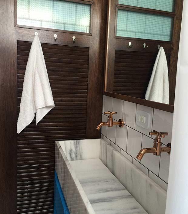O banheiro da suíte foi fechado com porta de correr com veneziana e vidro aramado na parte superior. Projeto de marcenaria da GM Madeiras. A bancada em formato de caixa é de mármore carrarinha branco (Foto: Divulgação/André de Freitas)