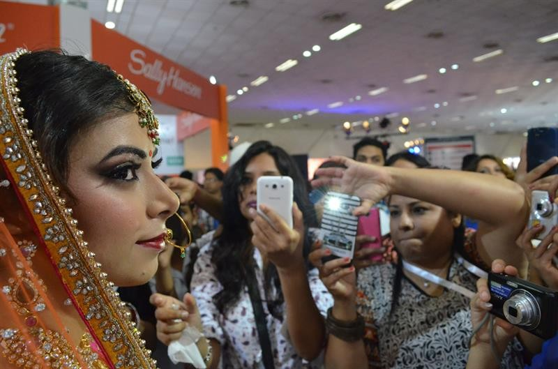 Mulheres fotografam modelo em feira da indústria cosmética na Índia (Foto: EFE)