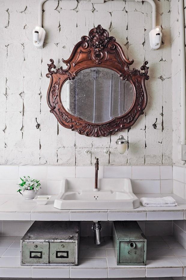 A parede descascada de azulejos traz um clima mais bruto, de desconstrução, enquanto o espelho entalhado propõe um pouco de delicadeza (Foto: Marcelo Magnani / Editora Globo)