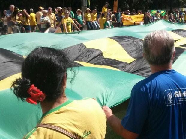 SÃO PAULO: Na Avenida Paulista, os manifestantes abrem uma grande bandeira e começam a cantar o Hino Nacional. (Foto: Gabriela Gonçalves/G1)