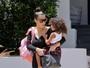 Kim Kardashian, de vestido justinho, chama a atenção pelas curvas