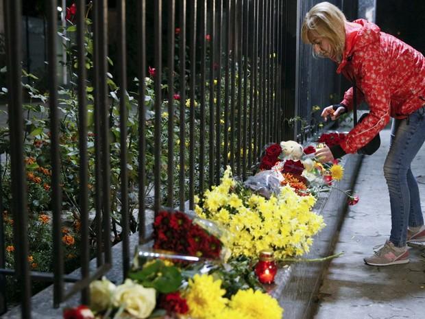 Mulher deposita flores na embaixada da Rússia em Kiev, na Ucrânia, em homenagem às vítimas da queda do avião russo no Sinai (Foto: REUTERS/Valentyn Ogirenko)