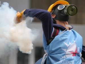 Manifestante atira bomba de gás durante protesto em Istambul, na Turquia (Foto: Emrah Gurel/AP)