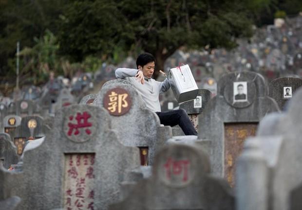 Homem visita jazigo de parente no Cemitério Diamond Hill em Hong Kong: já começa a faltar espaço para enterrar mortos na China (Foto: Jerome Favre/EFE)