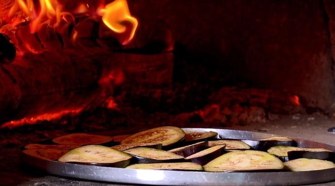 As rodelas de berinjela são levadas ao forna à lenha antes de colocar os queijos e o molho (Foto: reprodução EPTV)