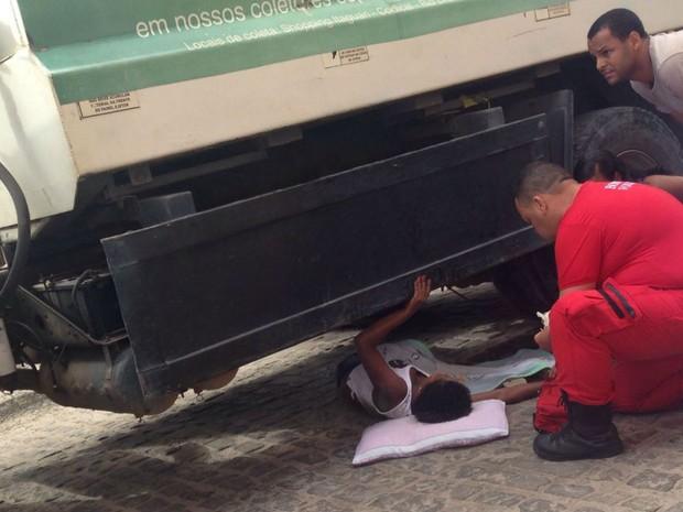 Mulher ficou presa embaixo do veículo depois de ser atropelada por caminhão de lixo na Bahia (Foto: Voz da Bahia / Sandy Santos)
