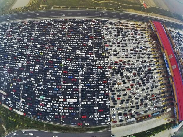 Foto tirada na terça (6) mostra milhares de veículos presos em um engarrafamento perto de um ponto de pedágio em Pequim, na China, durante a volta para casa após um feriado nacional (Foto: China Daily/Reuters)