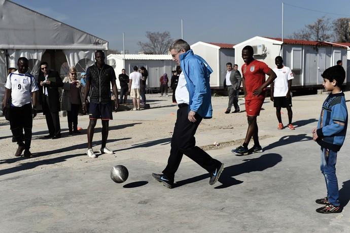 Thomas Bach joga futebol com crianças em campo de refugiados na Grécia (Foto: AFP)