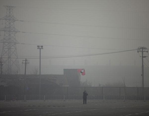 Homem solta pipa em Pequim, onde poluição em nível alarmante encobriu o céu nste sábado (12) (Foto: Alexander F. Yuan/AP Photo)
