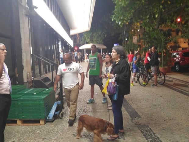 Maria Francisca (de pé, com o cão), foi presa suspeita de racismo contra Paulo (no celular) (Foto: Daniel Targueta/TV Globo)