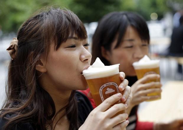 Em foto desta terça-feira (5), garotas apreciam cerveja com espuma congelada Em Tóquio. (Foto: Toru Hanai/Reuters)