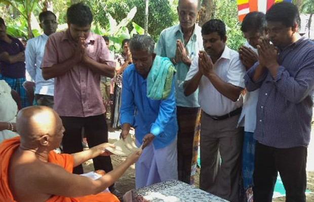 Mudiyanselage (de azul, à esquerda) assina documentos para entrega da terra a templo budista (Foto: BBC)