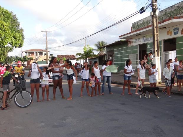 Com cartazes nas mãos, moradores cobram notícias de Davi da Silva (Foto: Michelle Farias/G1)