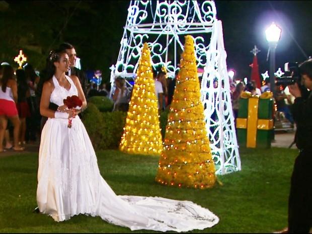 Noivos tiram fotos entre a decoração de Natal em Poços de Caldas, MG. (Foto: Reprodução EPTV)