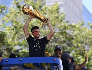 Stephen Curry comemorando no desfile com o caneco nas mãos (Foto: Justin Sullivan/Getty Images)