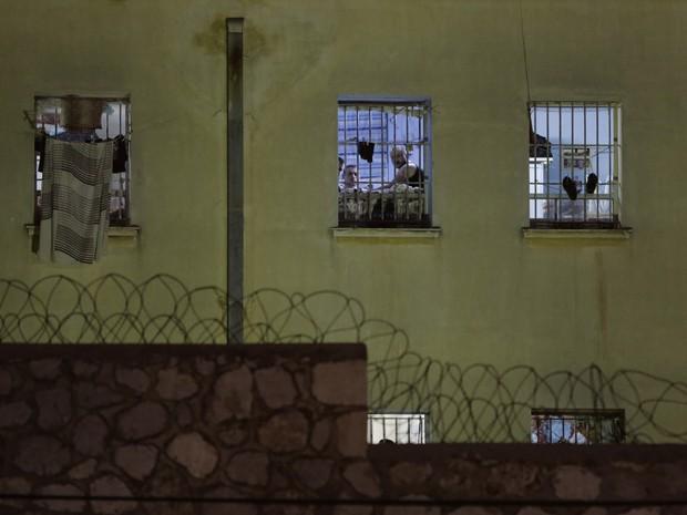 Presos são vistos nas janelas de celas da prisão Korydallos, em Atenas, no domingo (3) (Foto: AP Photo/Petros Giannakouris)