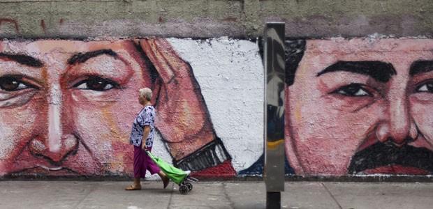 Mulher caminha em frente a desenho de Hugo Chávez e de Nicolás Maduro em Caracas (Foto: Leo Ramirez/AFP)