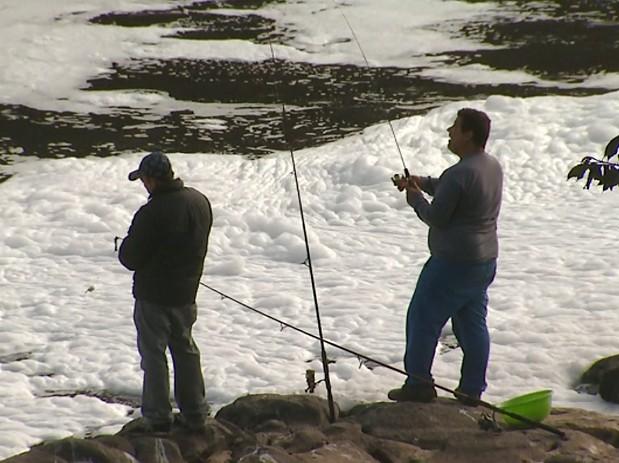 Homens pescam mesmo com espuma no Rio Piracicaba (Foto: César Fontenele/EPTV)