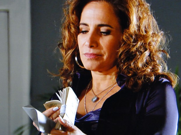 A traficante naõ se faz de rogada e confere a grana ali mesmo (Foto: Salve Jorge/TV Globo)