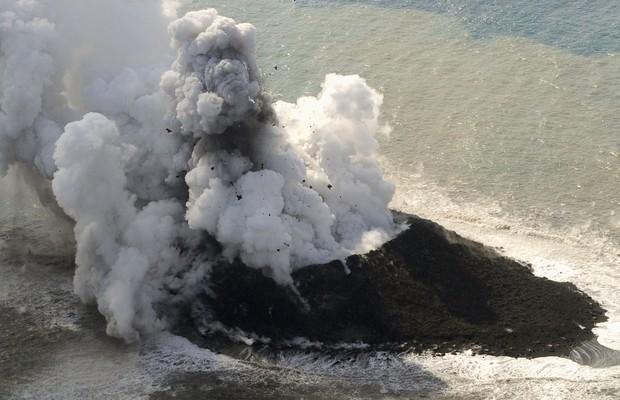 A nova ilhota formada na costa de Nishinoshima, ao sul do Japão, tem apresentado atividade vulcânica intensa (Foto: AP Photo/Kyodo News)
