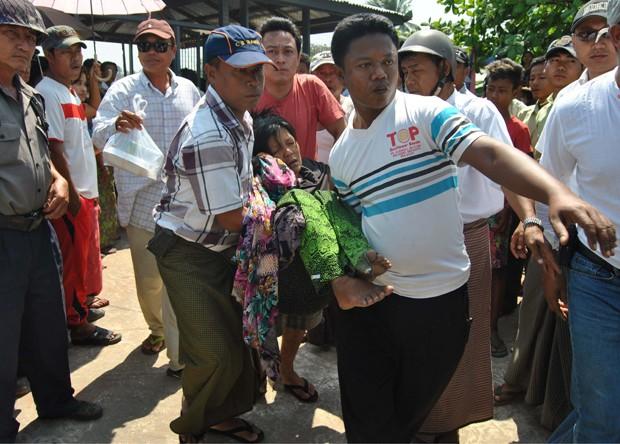 Sobrevivente é carregada após naufrágio de embarcação em Mianmar (Foto: STR/AFP)