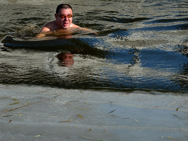 Chinês nada nas geladas águas do lago congelado Houhai, em Pequim, em uma temperatura de 3ºC, neste domingo (9). Nadar no inverno é popular especialmente entre idosos e aposentados no país. Eles acreditam que a prática traz benefícios à circulação e à saúde, além de melhorar a atenção, desestressar, remover dores e até trazer benefícios para rejuvenescimento da pele e promover o sentimento de bem-estar (Foto: Mark Ralston/AFP)