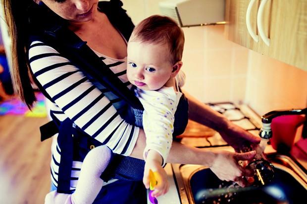 Mãe com bebê realizando tarefas domésticas (Foto: Thinkstock)