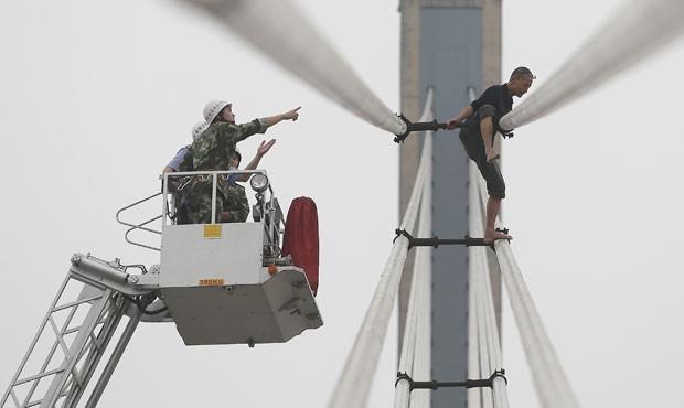 Homem tenta pular de ponte na China nesta segunda-feira (8) (Foto: Reuters)