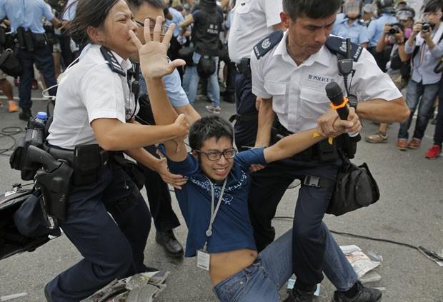 Manifestante pró-democracia é retirado pela polícia enquanto ambulância tenta sair do complexo do governo de Hong Kong nesta sexta-feira (3) (Foto: Vincent Yu/AP)