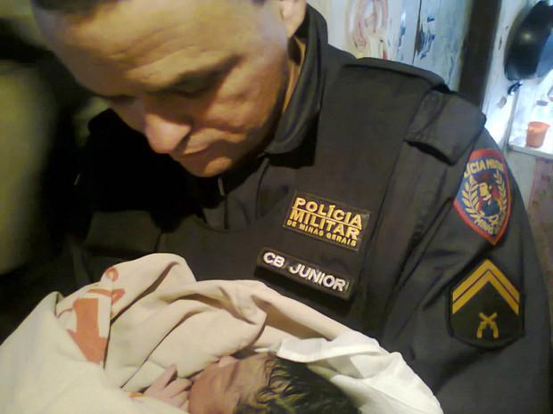 Cabo Júnior segurando o bebê após o parto realizado em casa por policiais (Foto: Polícia Militar)