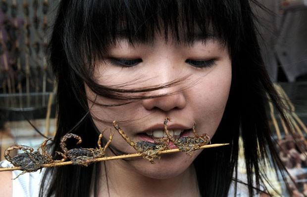 Chinesa come espetinho de escorpião em rua de Pequim, na China, em julho de 2008 (Foto: Mark Ralston/AFP)