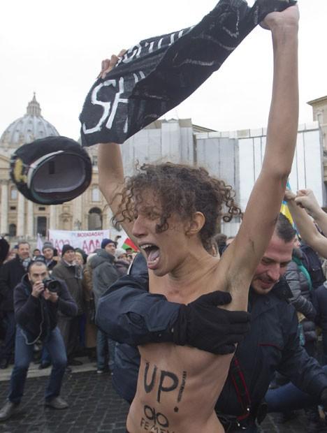 Policial italiano segura militante do grupo Femen, que realizou ato neste domingo na Praça de São Pedro, no Vaticano (Foto: Angelo Carconi/AP)