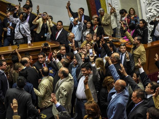 Deputados da oposição levantam as mãos ao votar pela abertura de processo político do presidente Nicolás Maduro, nesta terça-feira (25) na Assembleia Nacional em Caracas (Foto: JUAN BARRETO / AFP)
