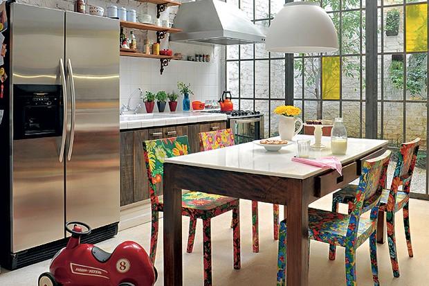 O piso de granilite foi escolhido pelo arquiteto Vitor Penha para harmonizar com o clima rústico dado pelo uso de madeira da marcenaria. As cadeiras de madeira forradas com chita resinada põem uma pitada de cor na cozinha (Foto: Marcelo Magnani)
