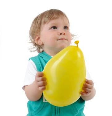 Bebê segurando bexiga (Foto: Shutterstock)