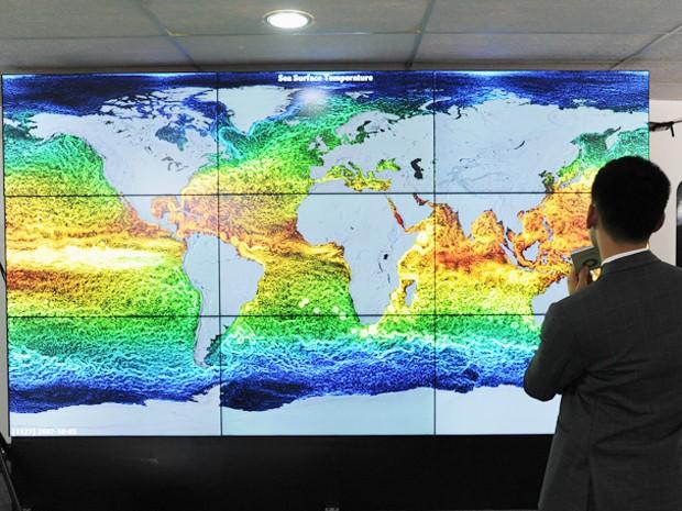 Participante da Conferência do Clima da ONU, a COP 20, observa mapa em telão que mostra a temperatura dos oceanos na Terra. As cores mais alaranjadas representam temperaturas maiores (Foto: UNFCCC)