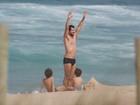 Daniel de Oliveira curte praia no Rio com os filhos e dá cambalhota