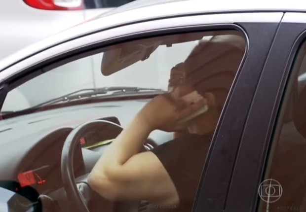 Homem fala ao celular enquanto dirige o carro: aumento de multas (Foto: Reprodução/Globo News)