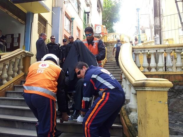 Defensor público detido passa mal e sai com paletó na cabeça para esconde rosto. (Foto: Juirana Nobres/ G1 )