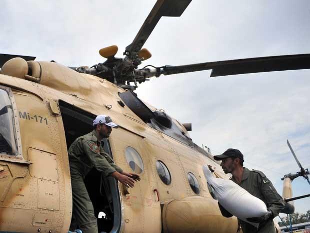Soldados paquistaneses carregam comida para sobreviventes (Foto: Hasham Ahmed / AFP Photo)