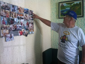 Marcos Rodrigues mostra fotos do centro de apoio a pacientes com câcer (Foto: Ana Carolina Caldeira/G1)