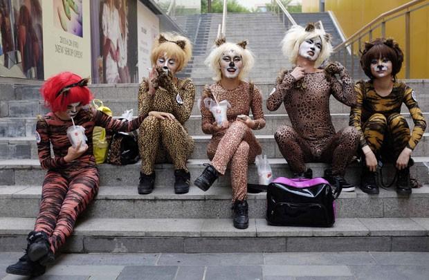Ativistas vestidas com roupas que lembram animais fazem performance em Pequim nesta quinta-feira (20) pedindo a proteção dos cães (Foto: Jason Lee/Reuters)