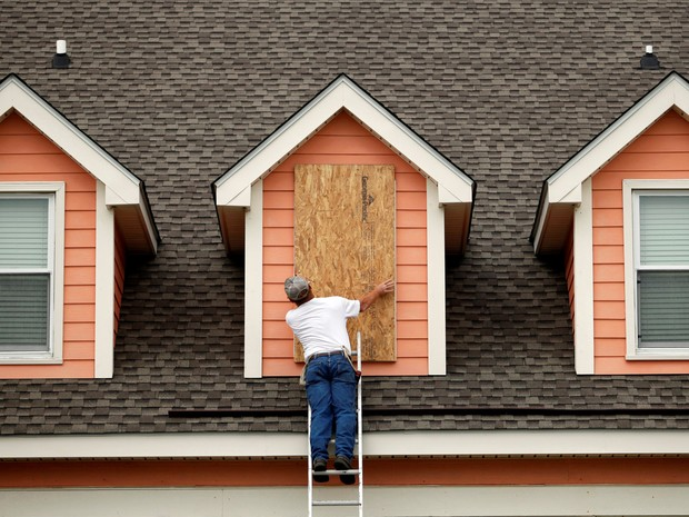 Brent Scurry instala proteção nas janelas de uma casa à beira-mar para se proteger com a chegada do furacão Matthew em Harden City Beach, na Carolina do Sul, nos EUA (Foto: Randall Hill/Reuters)