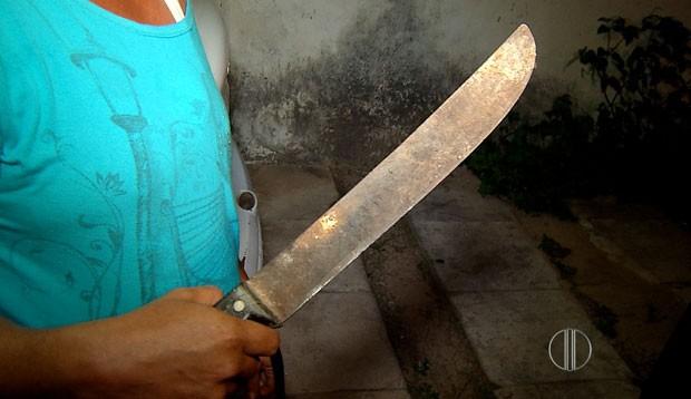 Filha, que também sofreu abuso sexual, segura o facão que foi usado pelo criminoso para ameaçá-la (Foto: Reprodução/Inter TV Cabugi)