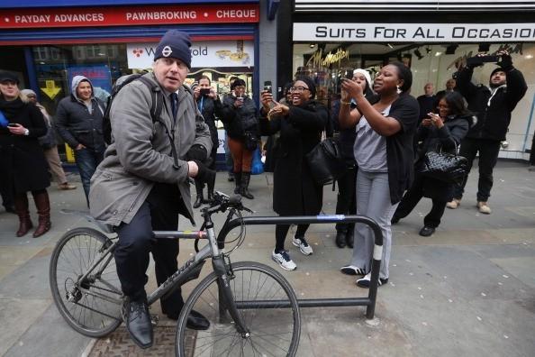 Pessoas tiram fotos do prefeito de Londres, Boris Johnson, que usa a bicicleta em vez de veículo oficial (Foto: Getty Images)