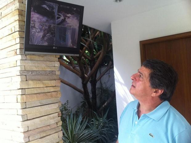 Morador observa imagens de câmeras de segurança instaladas em vias antes de deixar sua casa (Foto: Tatiana Santiago/G1)