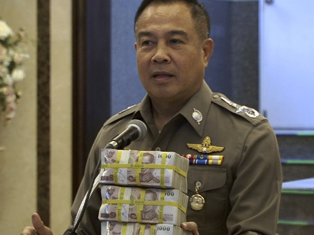 O chefe nacional da polícia da Tailândia, Somyot Poompanmoung, exibe a recompensa de 3 milhões de bahtes (US$ 84 mil) entregue à própria polícia após a prisão de um suspeito pelo atentado em um templo em Bangcoc, durante entrevista coletiva na segunda (31) (Foto: AP Photo/AP Video)