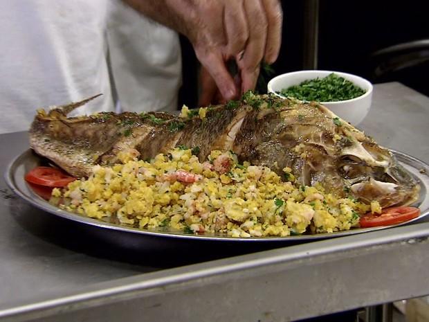 O peixe é servido com a farofa, tomates e azeitonas para decorar (Foto: Reprodução/Tv Tribuna)