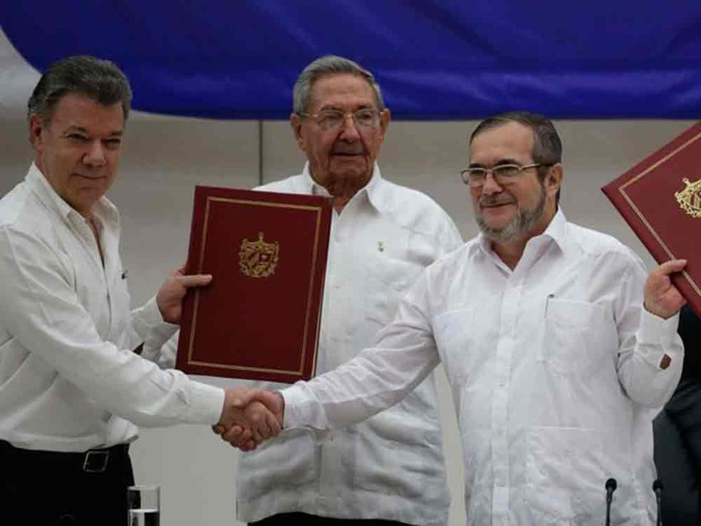 O presidente da Colômbia, Juan Manuel Santos (esq.), o presidente cubano Raúl Castro (centro) e o comandante das FARC Timoleón Jiménez (dir.) posan para fotos durante a cerimônia de assinatura do acordo de cessar-fogo bilateral definitivo em Havana (Foto: Ramón Espinosa/AP)